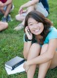 在电话联系的年轻人之外的亚裔女孩 免版税库存图片