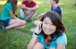 在电话联系的年轻人之外的亚裔女孩 免版税库存照片