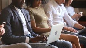 在电话膝上型计算机浸没的不同种族的人小组,占据心思被设备 影视素材
