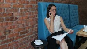 在电话读杂志和谈话坐在咖啡馆的蓝色沙发少妇的画象  股票录像