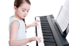 在电钢琴的小女孩戏剧。 免版税库存图片