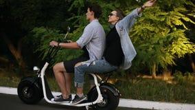在电镀自行车的愉快的夫妇骑马在街道在夏日 美丽的享受他们的时间的女孩和她的男朋友 影视素材