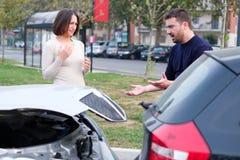 在男人和妇女之间的路愤怒,因为车祸 免版税库存图片