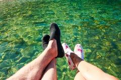 在男人和妇女的脚的最初人景色坐峭壁或码头在镇静清楚的水上在海岛 浪漫 库存照片