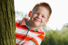 在男孩隐藏的结构树之后 图库摄影