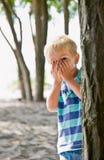 在男孩隐藏的结构树之后 免版税库存照片