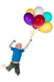 在男孩飞行之后的气球 图库摄影