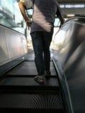 在男性后侧方,在自动扶梯的人立场的选择聚焦 免版税库存图片