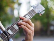 在男性手上的一张顶视图在被弄脏的背景的一个公园弹在一件牛仔裤夹克的吉他 免版税库存图片