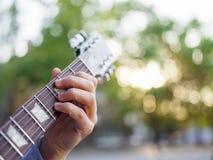 在男性手上的一张顶视图在被弄脏的背景的一个公园弹在一件牛仔裤夹克的吉他 库存照片