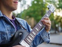 在男性手上的一张顶视图在被弄脏的背景的一个公园弹在一件牛仔裤夹克的吉他 免版税图库摄影