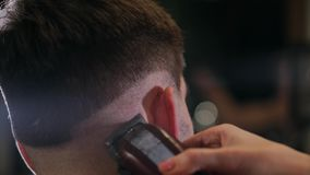 在男性的发型的特写镜头视图在与专业整理者的一家理发店 haircutting在美发店的人的与 股票录像