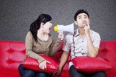 在男朋友的恼怒的女孩呼喊红色沙发的 免版税库存图片