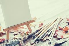 在画架、油漆管、刷子绘的和和秋天槭树叶子的帆布 免版税库存照片