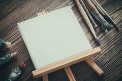 在画架、油漆管和刷子的帆布在木书桌上 库存照片