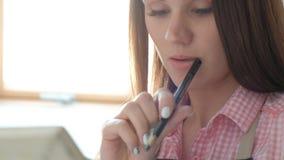 在画架和帆布中的年轻美女画家在一个明亮的演播室 启发和爱好 股票录像