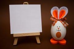 在画架的白色白纸用滑稽的鸡蛋以逗人喜爱的兔宝宝的形式在棕色背景的 库存照片