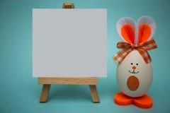在画架的白色白纸用滑稽的鸡蛋以逗人喜爱的兔宝宝的形式在蓝色背景的 库存图片