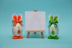 在画架的白色白纸用滑稽的鸡蛋以逗人喜爱的兔宝宝的形式在蓝色背景的 免版税库存照片
