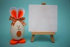 在画架的白色白纸用滑稽的鸡蛋以逗人喜爱的兔宝宝的形式在蓝色背景的 库存照片