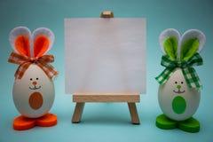 在画架的白色白纸用滑稽的鸡蛋以逗人喜爱的兔宝宝的形式在蓝色背景的 免版税库存图片