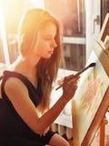 在画架的艺术家绘画在演播室 与刷子的女孩油漆 库存照片
