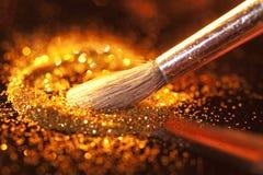 在画笔和光亮的粉末的特写镜头 免版税库存图片