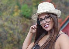 在画象帽子和玻璃年轻有吸引力的夏天秀丽之外的妇女 免版税库存图片