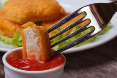 在番茄酱的一把叉子刺穿的鸡块 库存照片