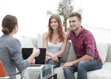 在疗期的年轻愉快的夫妇与家庭心理学家 免版税库存图片