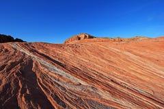 在疯狂的小山的镶边岩石在桃红色峡谷,在日落的火波浪附近,火国家公园,美国谷  图库摄影