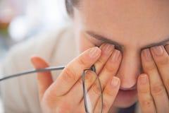 在疲乏的女商人的特写镜头有镜片的 免版税库存照片