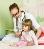 在病的坐的温度计附近供女孩小母亲住宿 免版税图库摄影
