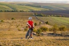 在登山车的骑自行车的人游客旅行 秋天横向 自行车的运动员在红色球衣和白色盔甲 免版税库存图片