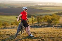 在登山车的骑自行车的人游客旅行 秋天横向 自行车的运动员在红色球衣和白色盔甲 免版税图库摄影