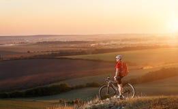 在登山车的骑自行车的人游客旅行 秋天横向 自行车的运动员在红色球衣和白色盔甲 免版税库存照片