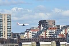 在登陆的大厦之间的飞机飞行 库存图片