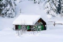 在白云岩的雪的小瑞士山中的牧人小屋 免版税图库摄影