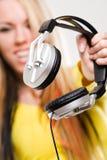 在白人妇女年轻人的有吸引力的耳机 免版税图库摄影