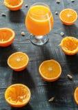 在白兰地酒的一块玻璃新近地紧压了橙汁过去 在玻璃旁边是切的桔子和热心黑暗的背景 E 免版税库存图片