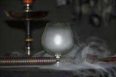 在白兰地酒玻璃下的重的水烟筒烟在灰色背景,水烟筒管 免版税库存照片
