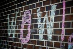 在白垩写的字哇在砖墙 库存照片