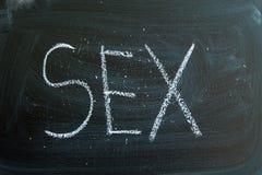 在白垩写的性在黑板 免版税库存图片