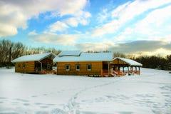 在白天冬天期间,休息的三个明亮的黄色房子在一个多雪的草甸中间在森林里 莫斯科 免版税图库摄影