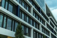 在白天的完善的现代办公楼 蓝色颜色,门面,几何样式 库存照片