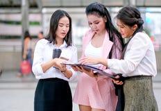 在白天,三个企业亚裔女孩一起谈论关于他们的工作在办公室外 免版税库存照片