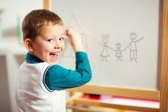在白板的逗人喜爱的小男孩图画有毛毡笔和微笑的 免版税图库摄影