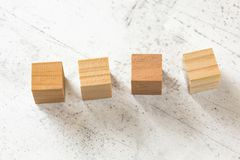 在白水泥板的四个空白的木立方体 图库摄影