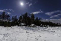 在白海的一个冻海湾的岸的木小屋在村庄Nilmoguba附近的在被月光照亮夜 卡累利阿 库存照片