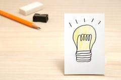 在白皮书和文具的电灯泡图画作为背景 库存图片